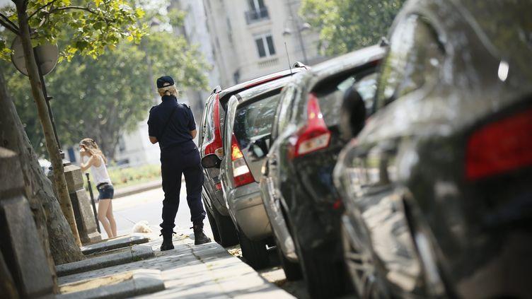 Un agent de surveillance de la ville de Paris verbalise une voiture le 17 juillet 2013. (MAXPPP)