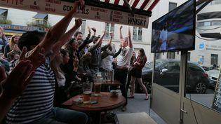 Des supporters célèbrent un but de la France contre la Suisse en Coupe du monde, le 20 juin 2014 à Paris. (JACQUES DEMARTHON / AFP)