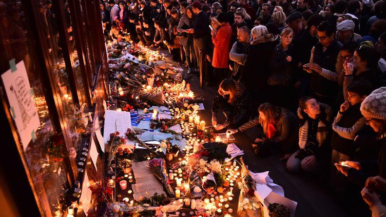 Des fleurs et des bougies sont déposées à la terrasse du bar Le Carillon, le 15 novembre 2015.L'établissement a été visé l'avant-veille par des terroristes ayant mené une série d'attaques coordonnées qui ont fait 130 morts à Paris et Saint-Denis. (LOIC VENANCE / AFP)