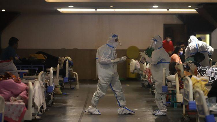 Des médecins s'occupent de patients Covid-19 au Shehnai Banquet Hall, temporairement converti en salle d'isolement, à New Delhi, en Inde, le 21 avril 2021. (AMARJEET KUMAR SINGH / ANADOLU AGENCY / AFP)