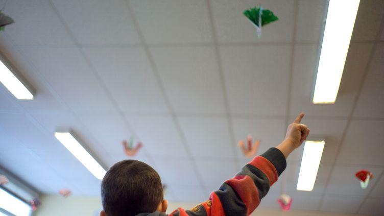 Un élève d'une classe de primaire lève le doigt pour prendre la parole dans une école de Mulhouse (Haut-Rhin), en février 2013. (SEBASTIEN BOZON / AFP)