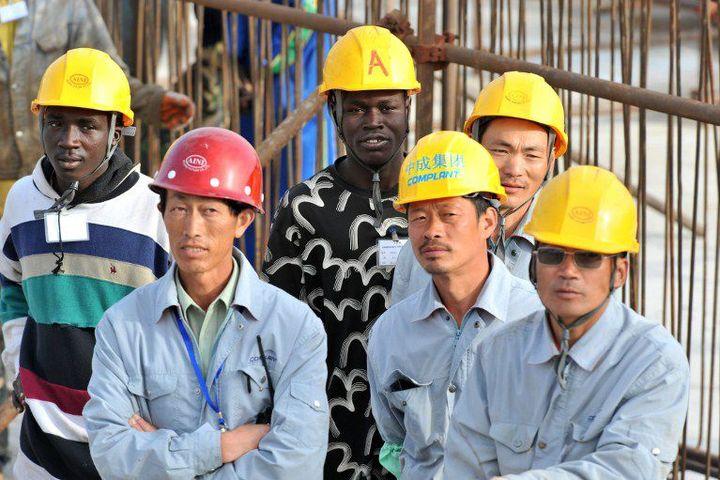 Des ouvriers chinois et sénégalais sur un site de construction financé par la Chine à Dakar au Sénégal. (Photo AFP/Seyllou Diallo)