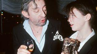 """Serge Gainsbourg avec sa fille Charlotte, le 22 février 1986 à Paris, lors de la cérémonie des César où Charlotte a reçu le César du meilleur jeune espoir féminin pour son rôle dans le film de Claude Miller """"L'Effrontée"""".  (MICHEL GANGNE / AFP)"""