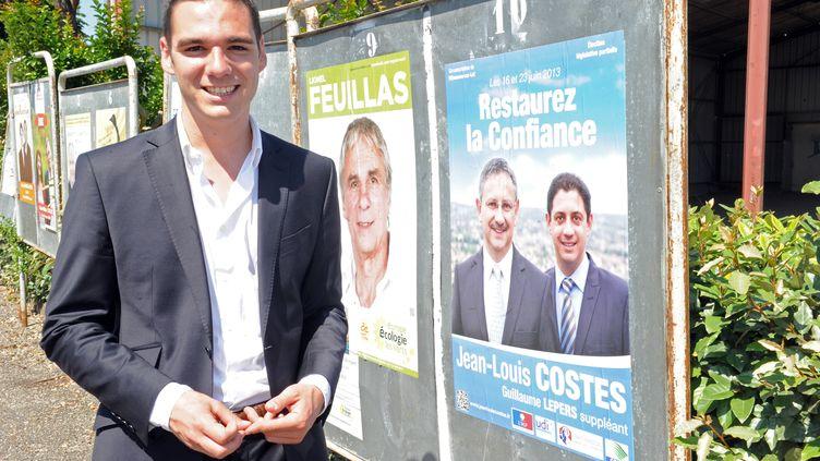 Le candidat FNEtienne Bousquet-Cassagne pose devant l'affiche électorale de son adversaire UMP Jean-Louis Costes, le 16 juin 2013, à Villeneuve-sur-Lot (Lot-et-Garonne). (MEHDI FEDOUACH / AFP)