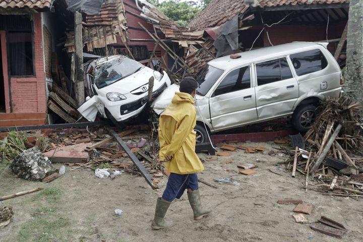 Un homme observe des voitures déplacées par un tsunami et projetées dans des habitations, à Carita (Indonésie), le 23 décembre 2018. (DIAN TRIYULI HANDOKO / AP / SIPA)