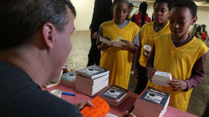 """L'écrivain pour la jeunesse Jeff Kinney dédicace son livre """"Journal d'un dégonflé - Ca déménage"""", (Seuil Jeunesse), le 10 décembre 2019 (Laurence Houot / franceinfo Culture)"""