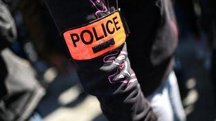 """Un homme porte un brassard """"police"""" lors d'une manifestation à l'extérieur du palais de justice de Paris, le 20 avril 2021. (CHRISTOPHE ARCHAMBAULT / AFP)"""