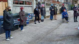 Un groupe de voisins regarde la cérémonie d'investiture de Joe Biden dans le quartier d'AU Park à Washington (Etats-Unis), le 20 janvier 2021. (VALENTINE PASQUESOONE / FRANCEINFO)
