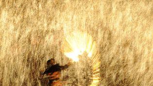 Un forgeron lance du métal fondu contre un mur froid pour créer des étincelles dans le cadre des célébrations du festival des lanternes à Nuanquan (Chine), le 6 février 2012. (MARK RALSTON / AFP)