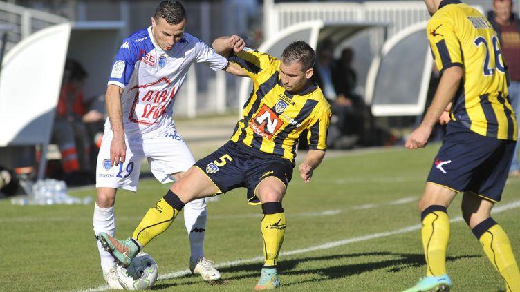 Les joueurs d'Arles la saison dernière (en jaune et noir), ici face à Troyes en L2 (?FABRICE FOURES / MAXPPP)