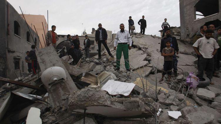 Des Palestiniens inspectent les ruines d'une maison dans le camp de Jebaliya dans le Nord de la bande de Gaza, samedi 17 novembre 2012. (HATEM MOUSSA / SIPA)