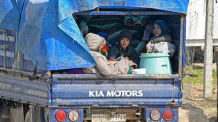 Des enfants syriens à l'arrière d'un camion, sur la route en direction d'Afrin et Azaz, près de la frontière turque, le 14 février 2020. (RAMI AL SAYED / AFP)