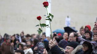 """Dans la foule, des manifestants ont brandi des roses, en hommage aux victimes des attentats, et des crayons, la seule arme dont disposaient les dessinateurs de """"Charlie Hebdo"""" face à leurs assassins. (CHARLY TRIBALLEAU / AFP)"""