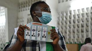 Une responsable de la commission électorale lors du décompte des votes dans un bureau, à Abidjan le 31 octobre 2020 (ISSOUF SANOGO / AFP)