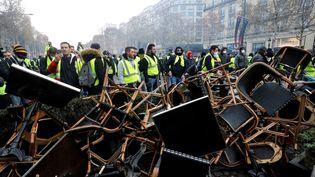 """Les """"gilets jaunes"""" ont rassemblé des dizaines de chaises des cafés et brasseries donnant sur les Champs-Elysées. (FRANCOIS GUILLOT / AFP)"""