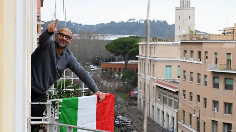 Un Italien sur son balcon à Rome, pendant l'épidémie de coronavirus, en Italie. (TIZIANA FABI / AFP)