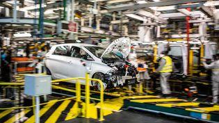 Des employés travaillent sur la chaîne de montage qui produit à la fois le véhicule électrique Renault Zoe et le véhicule hybride Nissan Micra, à Flins-sur-Seine, (Yvelines), le 6 mai 2020. (MARTIN BUREAU / AFP)