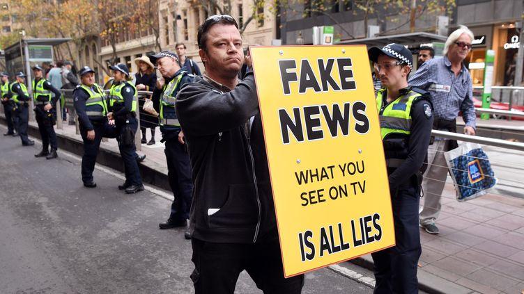 """Un manifestant en Australie brandit une pancarte où est inscrit """"Fake news, ce que vous voyez à la télévision n'est que mensonge"""" (WILLIAM WEST / AFP)"""