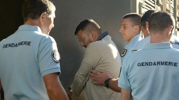 Des gendarmes français escortent au tribunal de Marseille un homme suspecté d'avoir vendu un bébé, le 1er septembre 2013. (BORIS HORVAT / AFP)