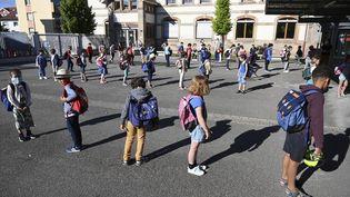 Des élèves font la queue avant d'entrer en classe, à l'école élémentaireZiegelau à Strasbourg (Bas-Rhin), le 22 juin 2020. (FREDERICK FLORIN / AFP)