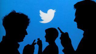 Le logo Twitter derrière un groupe de personnes, le 27 septembre 2013, à Varsovie (Pologne). (KACPER PEMPEL / REUTERS)