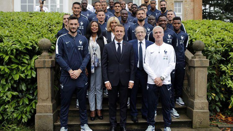 Emmanuel et Brigitte Macron posent avec les joueurs de l'équipe de France de fooball et la ministre des Sports Laura Flessel, àClairefontaine-en-Yvelines, en banlieue parisienne, le 5 juin 2018. (FRANCOIS MORI / AFP)