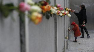 Des Berlinois déposent des fleurs sur un segment du mur de Berlin, le 9 novembre 2014. (FABRIZIO BENSCH / REUTERS)