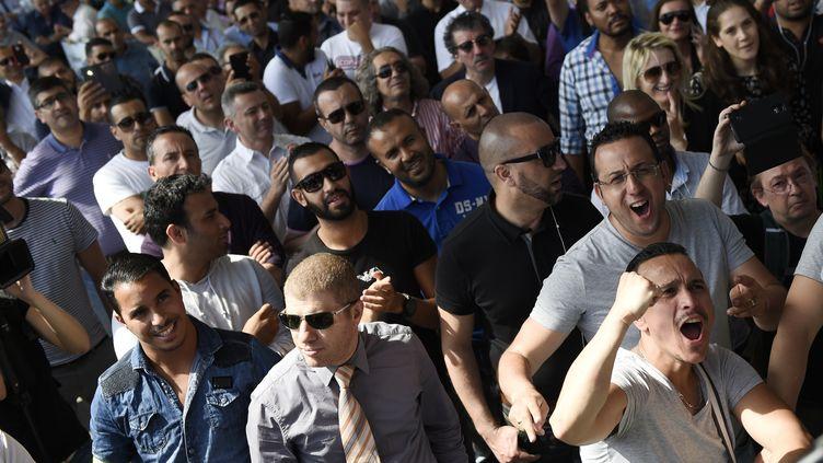 Des chauffeurs de taxi écoutent le président de la Fédération des taxis indépendants annoncer la tenue d'une réunion au ministère de l'Intérieur, jeudi 25 juin 2015, alors qu'ils manifestent porte Maillot à Paris. (LOIC VENANCE / AFP)