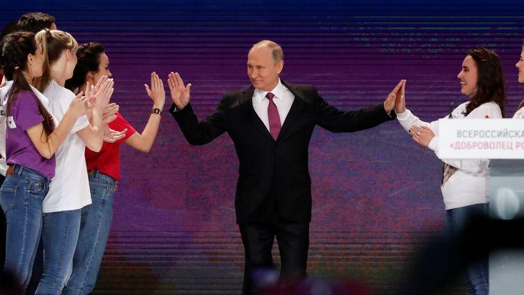 Vladimir Poutine salue des militants lors de son arrivée à un congrès de bénévoles de diverses ONG, le 6 décembre 2017 à Moscou (Russie). (SERGEI KARPUKHIN / REUTERS)