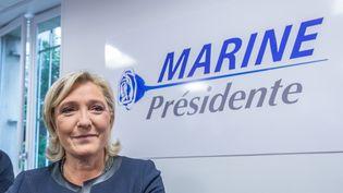 Marine Le Pen, présidente du Front national, devant son nouveau logo lors del'inauguration de ses locaux de campagne, à Paris, le 16 novembre 2016. (JULIEN MATTIA / NURPHOTO / AFP)