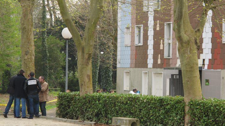 Des membres de la police scientifique près de l'immeuble où une femme de 47 ans a été tuée, le 5 avril 2012 à Grigny (Essonne). (JULIEN HEYLIGEN / LE PARISIEN / MAXPPP)