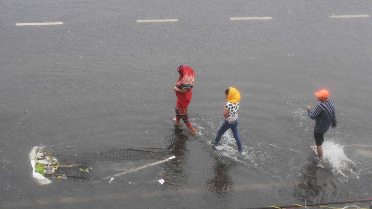 Des habitants de Puri (Inde) tentent dese déplacer dans les rues inondées par le cyclone Fani, le 3 mai 2019. (DIBYANGSHU SARKAR / AFP)