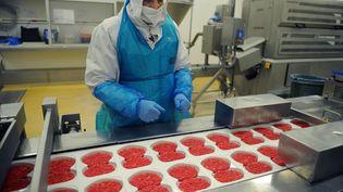Un employé de la société Spanghero travaille sur une chaîne de production de steaks hachés, le 23 juin 2011 à Castelnaudary (Aude). (REMY GABALDA / AFP)