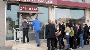 Une file d'attente devant un distributeur de la banque Laiki, le 21 mars 2013 à Nicosie (Chypre). (HASAN MROUE / AFP)