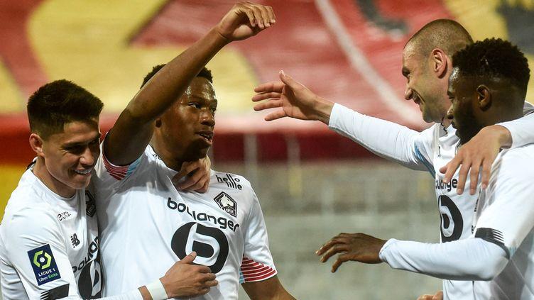 Les Lillois heureux autour de Jonathan David et Burak Yilmaz, les buteurs à Lens lors du derby du Nord, le 7 mai 2021. (FRANCOIS LO PRESTI / AFP)