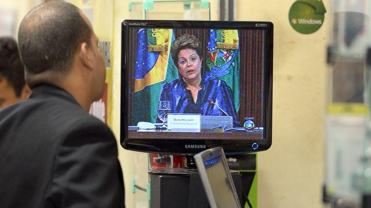 Un vendeur de Rio de Janeiro (Brésil) regage la présidente du Brésil Dilma Roussef annoncer à la télévision un plan d'investissements pour les transports, le 24 juin 2013. (YASUYOSHI CHIBA / AFP)