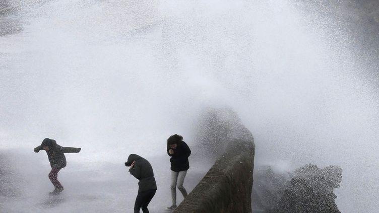 Des promeneurs sur le front de mer se font doucher par les vagues pendant la grande marée à Biarritz (Pyrénées-Atlantiques), le 24 février 2015. (REGIS DUVIGNAU / REUTERS)