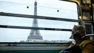 Une passagère dans le métro parisien passe devant la tour Eiffel, le 5 mai 2020. (ELKO HIRSCH / HANS LUCAS)