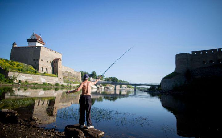 Un homme pêche sur la Narva, côté estonien, en juin 2016. Le château d'Hermann, à gauche, fait face à la forteresse d'Ivangorod, situé sur la rive russe du fleuve. (KAY NIETFELD / DPA)