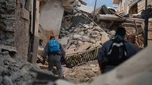 Des secours cherchent des victimes sous un immeuble endommagé à Amatrice (Italie) le 24 août 2016. (FILIPPO MONTEFORTE / AFP)