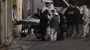 Des policiers évacuent un corps après l'intervention antiterroriste à Saint-Denis (Seine-Saint-Denis), le 18 novembre 2015. (ERIC FEFERBERG / AFP)
