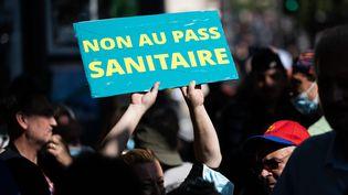 Un manifestant brandit un panneau anti-pass sanitaire lors d'un rassemblement devant le Sénat, jeudi 22 juillet. (ALEXIS SCIARD / MAXPPP)