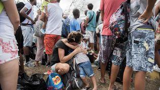 Une mère et son enfant attendent de quitter l'île de Saint-Martin, le 10 septembre 2017. (MARTIN BUREAU / AFP)