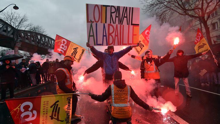 """Le manifestant Jean-Baptiste Redde lève une pancarte oùsont inscrits les mots """"Loi Travail à la baille"""", le 31 mars 2016 à Paris. (ALAIN JOCARD / AFP)"""