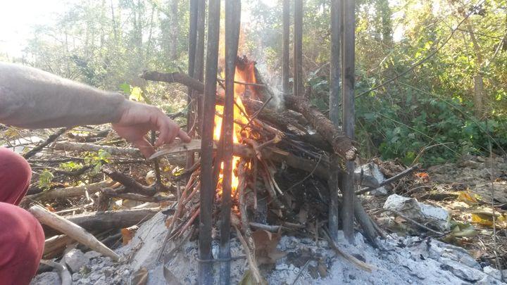 Un opposant tente de faire fondre les structures métalliques d'un poteau électrique, afin d'ériger une barricade, sur le site du projet de barrage de Sivens (Tarn), en octobre 2014. (FABIEN MAGNENOU / FRANCETV INFO)