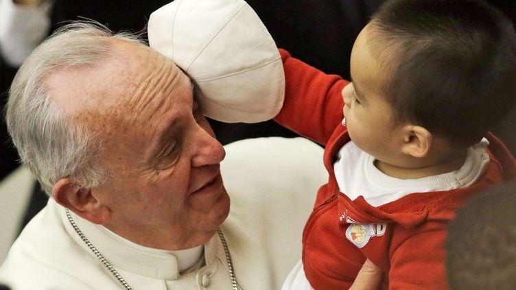 Un enfant dérobe au pape François, au Vatican, le 14 décembre 2013. (GREGORIO BORGIA / AP / SIPA)