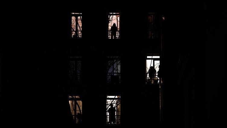 Parisiensà leur balcon, en mars 2020. (PHILIPPE LOPEZ / AFP)