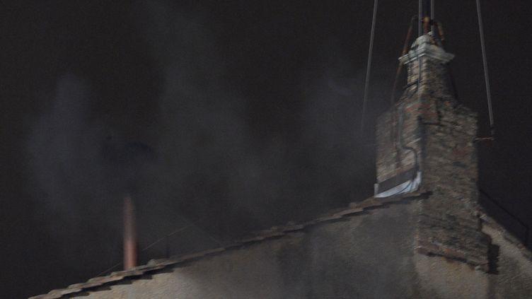 De la fumée noire s'échappe de la chapelle Sixtine, le 12 mars 2013, au Vatican. (VINCENZO PINTO / AFP)