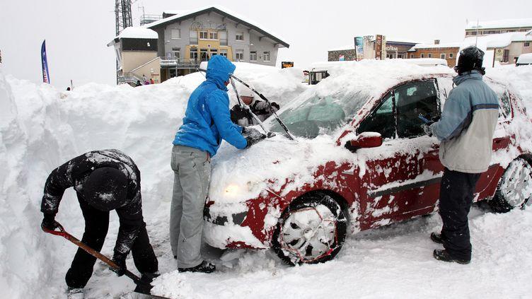 Des automobilistes déneigent une voiture à Saint-Lary-Soulan (Hautes-Pyrénées), le 1er février 2015. (LAURENT DARD / AFP)