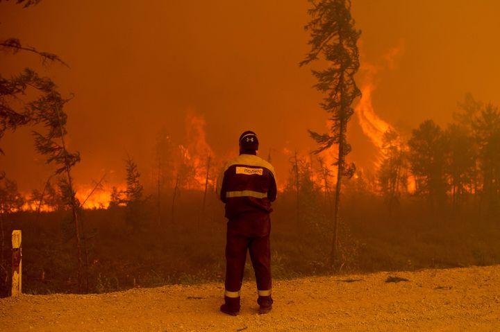 Un pompier se tient sur les lieux d'un incendie de forêt près du village de Kyuyorelyakh(Russie), le 7 août 2021. (IVAN NIKIFOROV/AP/SIPA / SIPA)